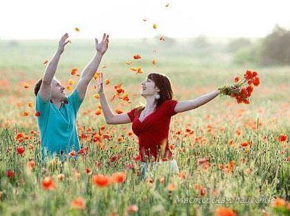 на поле мужчина и женщина радуются природе